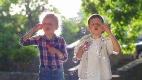 在使用在背后照明的新鲜空气的公园的愉快的童年、女孩和男孩吹的肥皂泡 股票视频