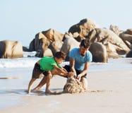 在使用的海滩的愉快的家庭,有儿子走的沿海的父亲 免版税库存图片