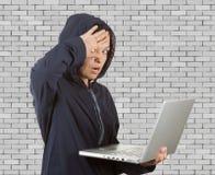 在使用膝上型计算机的Catched犯罪妇女黑客佩带的敞篷 库存照片