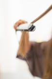 在使用头发直挺器的少妇的特写镜头 免版税库存图片