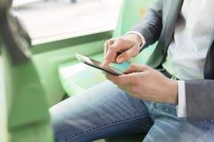 在使用他的手机的公共汽车人 读书电子邮件 短信的messag 图库摄影