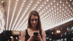 在使芝加哥剧院惊奇的愉快的美好的微笑的地方妇女身分使用智能手机信使,朝左边看 股票录像