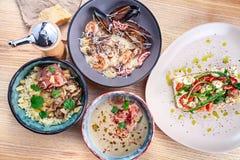 在供食的食物的顶视图在白色木桌上 意大利烹调bruschetta、jamon奶油色汤、意大利煨饭和海鲜面团午餐的 库存照片