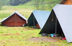 在侦察员的野营的帐篷在山的草坪野营 库存照片