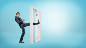 在侧视图的一个商人踢一个小白色门开放与他的在蓝色背景的腿 免版税图库摄影