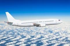 在侧视图的乘客白色飞机,在飞行水平面天空的飞行 免版税库存照片