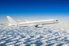在侧视图的乘客白色飞机,在飞行水平面天空的飞行 图库摄影