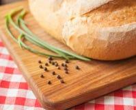 在侧视图的有壳的大面包在木桌上用胡椒和葱 免版税库存照片