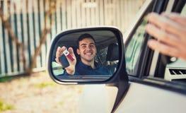 在侧视图镜象反射的偶然人司机陈列汽车钥匙 成功的年轻人买了一辆新的汽车 免版税库存照片