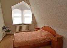 在便宜的旅馆有双重斜坡屋顶的房屋的地板上的双人房间  图库摄影