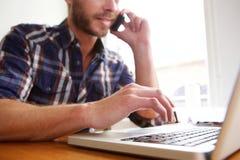 在便携式计算机上的人和谈话在电话 免版税库存照片