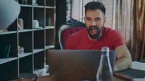 在便携式计算机上的愉快的商人读的好消息在办公室 背景查出的符号白色是 股票录像