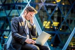 在便携式计算机上的沮丧的商人 库存照片