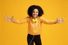 在便服和耳机有灿烂微笑的可爱的非裔美国人的年轻女人打扮的准备好拥抱  免版税库存照片