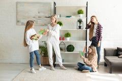 在便服的年轻可爱的女同性恋的家庭一起花费时间的在客厅 免版税图库摄影