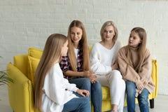在便服的年轻美丽的女同性恋的家庭在家坐黄色沙发 免版税库存照片