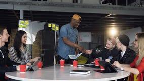 在便服穿戴的美国黑人的商人做握手在与白种人同事的一次会谈上在 股票录像