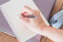 在便条纸的手文字在工作场所 免版税库存照片
