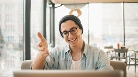 在便衣和镜片的英俊的商人在咖啡馆使用一台膝上型计算机 库存照片