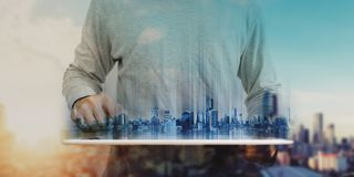 在便衣的商人使用数字式片剂,有全息图未来派现代大厦的 房地产和技术概念 免版税图库摄影