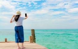 在便装样式采取selfie的用途智能手机的年轻亚洲女服草帽在木码头 在热带天堂的暑假 库存图片