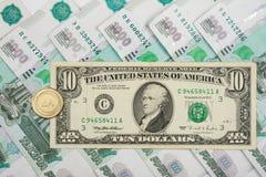 在俄罗斯卢布是10枚美国美元和硬币与题字 免版税库存图片