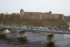 在俄罗斯和爱沙尼亚之间的过境桥梁通过Ivangorod堡垒的背景的,多云天纳尔瓦河 库存图片
