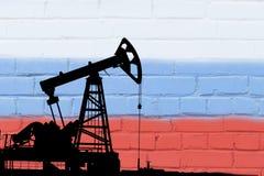 在俄罗斯联邦的旗子的背景的石油钻井 库存图片