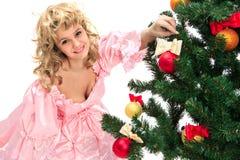 在俏丽的立场结构树附近的圣诞节女&# 免版税库存照片