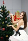 在俏丽的结构树附近的圣诞节女孩 免版税库存照片
