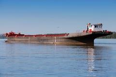 在保加利亚和R之间的多瑙河停住的大货物驳船 库存照片