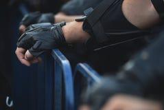 在保护篱芭的保安人员手在暴乱期间 库存照片