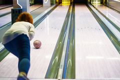 在保龄球俱乐部的少妇投掷的球 免版税图库摄影