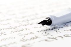 在信件的白色钢笔 免版税库存照片