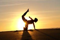 在信奉瑜伽者主要形成的剪影后的明亮的阳光 免版税库存照片
