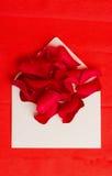 在信封的一些红色玫瑰花瓣在红色 免版税库存照片