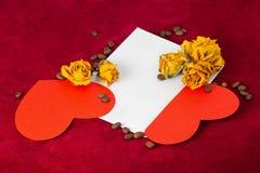 在信封的两红色心脏与干玫瑰和咖啡豆 免版税图库摄影