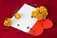 在信封的红色心脏与干玫瑰和咖啡豆 图库摄影