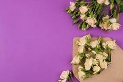 在信封的美丽的微型玫瑰与在明亮的淡紫色背景的笔记薄 节假日 日s华伦泰 日s妇女 顶视图 Sp 库存图片