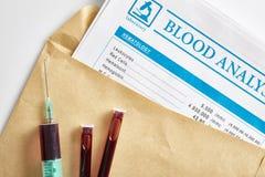 在信封的血液报告与小瓶和注射器有血液的 免版税图库摄影