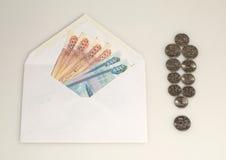 在信封的金钱和从硬币的惊叹号 免版税库存图片