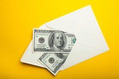 在信封,在财务概念的金钱的钞票,隔绝在黄色背景中 库存图片