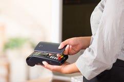 在信用卡机器附近的巧妙的手机,票据可以被支付这样 免版税库存图片