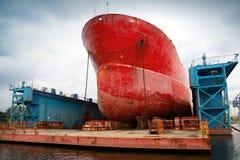 在修理下的大红色罐车在浮船坞 免版税库存照片
