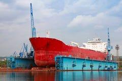 在修理下的大红色罐车在蓝色浮船坞 免版税库存照片