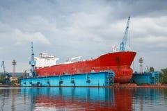 在修理下的大红色罐车在蓝色浮船坞 免版税库存图片