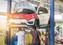 在修理在车库的停止的推力的汽车与工作在被举的汽车下的机械工对变速轮插孔 库存图片