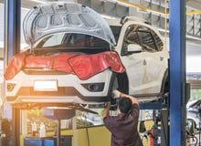 在修理在车库的停止的推力的汽车与工作在被举的汽车对变速轮插孔和维护下的机械工关于 免版税库存照片