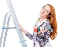 在修理期间的主妇,在一架梯子的画象与工具 免版税库存照片