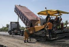 在修路和修理期间的工作者经营的沥青摊铺机机器运转 摊铺机修整机,沥青修整机 免版税库存照片